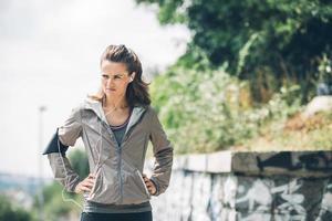 mujer corredor con las manos en las caderas mirando a distancia foto