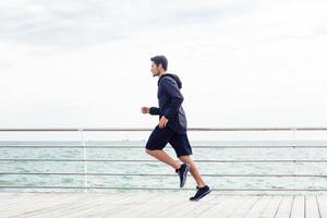 hombre deportivo corriendo cerca del mar foto