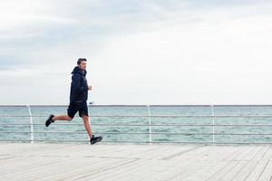 hombre deportivo corriendo cerca del mar o foto