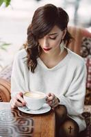 Young girl drinking coffee in a trendy cafe photo