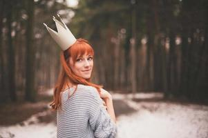 Young woman with crown in forest. photo