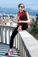 Sporty woman on the park alley with city view photo