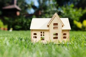Wooden model of house on grass,  summer outdoor, new home