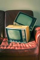 Two vintage televisions on red couch photo