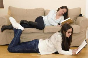 Two women lying on sofa reading