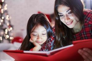Daughter with her mother read a book by the Christmas