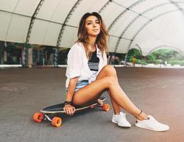 estilo de vida de moda, hermosa mujer joven con longboard