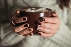 Brown cup with cocoa and marshmallow in the hands