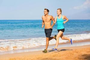 Couple running on the beach photo