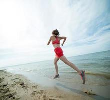jonge dame draait op het zonnige zomer zandstrand. training