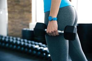 Closeup image of a woman holding dumbbells