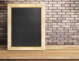 Blank blackboard on wooden table at red brick wall