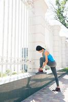 Young woman runner tying shoelaces photo