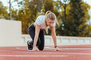 Woman standing in start position for run photo