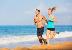 pareja corriendo en la playa foto