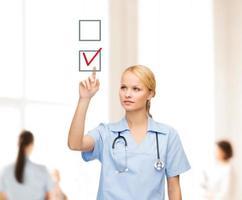 sonriente médico o enfermera apuntando a la marca de verificación