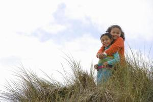 Sisters embracing on sand dune, smiling, portrait, low angle vie photo