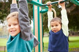 Two Young Boys On Climbing Frame In Playground