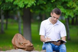 Young man studying for college exam in park outside photo