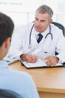 medico serio che prescrive farmaco al suo paziente