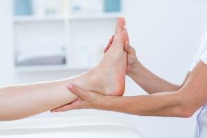 fisioterapeuta haciendo masaje de pies foto