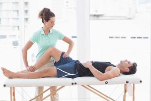 Doctor examining man leg photo