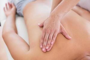 fisioterapeuta haciendo masaje de espalda a su paciente foto