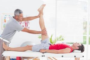 Physiotherapist doing leg stretching to his patient photo