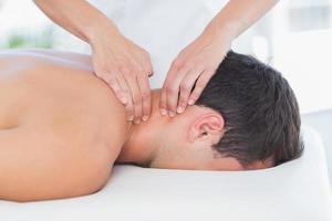 Fisioterapista che fa massaggio al collo al suo paziente