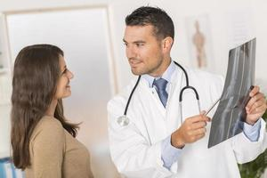 Médico que muestra el resultado de la radiografía al paciente foto