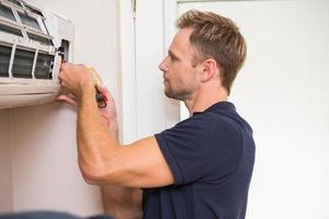 Focused handyman testing air conditioning photo