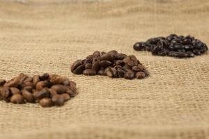 diferentes grados de tostado de granos de café, fondo textil de yute foto