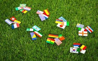 Corte de papel de banderas en el césped para el campeonato de fútbol 2014 foto