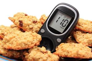 Glucometer and oatmeal cookies on white background