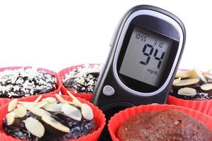 Glucometer and chocolate muffins in red cups