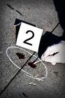 Una escena del crimen con sangre en el hormigón con la etiqueta 2 foto