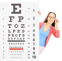 Teenage girl with glasses standing behind eyesight test photo