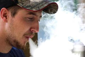 Man Looks Down and Exhales Vape Mist