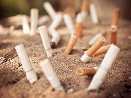 muchos cigarrillos quemados en cenicero y arena foto