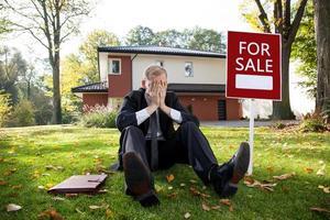 agente inmobiliario cansado está sentado en el césped foto
