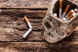 sigaretta nel posacenere a forma di teschio