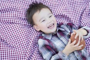 Joven muchacho de raza mixta jugando con fútbol en manta de picnic