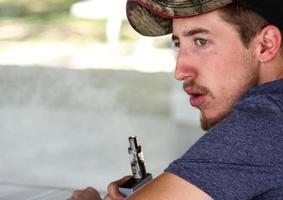 Man Sitting Down While Holding E-Cigarette Device