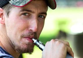 Man Inhales From an E-Cig Device