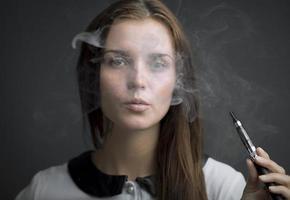 elegante mujer fumando cigarrillo electrónico con humo