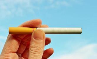vaping ecigarettes de vapor con batería electrónica contra el cielo foto