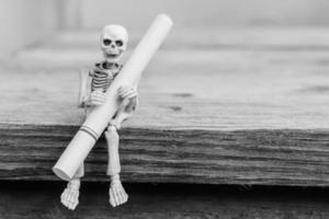 esqueletos con cigarrillo sentarse en la mesa de madera, enfoque selectivo