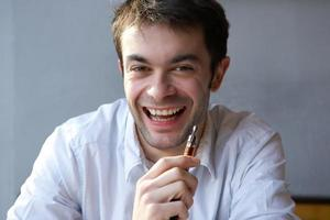 Happy young man holding electric cigarette photo