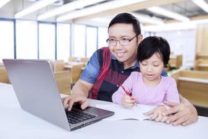 tutor usando laptop mientras enseña a su alumno foto