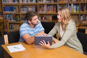 estudiante recibiendo ayuda del tutor en la biblioteca foto
